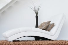 biały nowoczesny fotel na włochatym brązowym dywanie